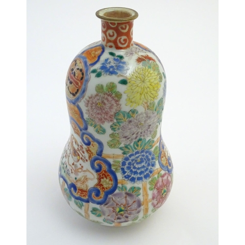 1 - A Chinese gourd vase with famille rose decoration depicting flowers, bamboo and birds. Character mar...