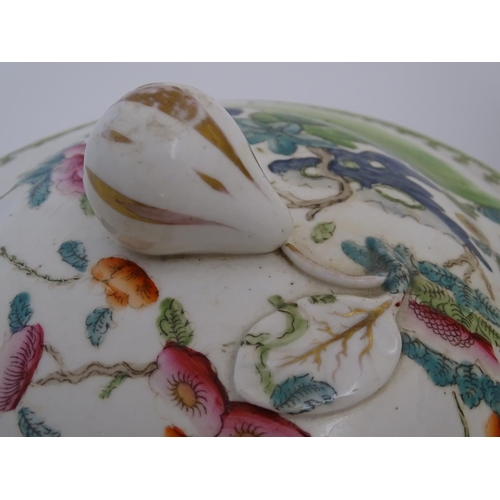 11 - A Chinese tureen and cover with twin handles decorated with a stylised landscape with a tree and flo...