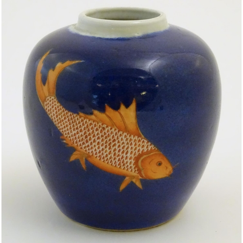 13 - A Chinese vase with a cobalt blue ground decorated with three hand painted fish. Approx. 5 1/2