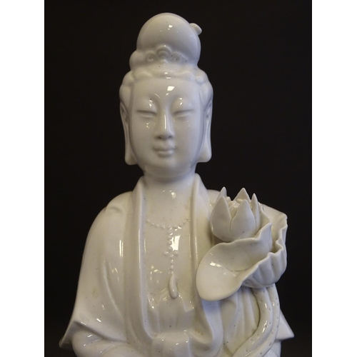 19 - A Chinese blanc de chine figure of Guanyin standing holding flowers, raised on a base of lotus flowe...