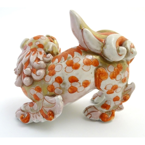 24 - A Chinese ceramic figure formed as a stylised foo dog / temple guardian with gilt highlights. Approx...