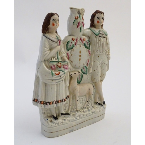 32 - A Victorian Staffordshire flatback figural group depicting a man and woman with a deer flanking a cl...