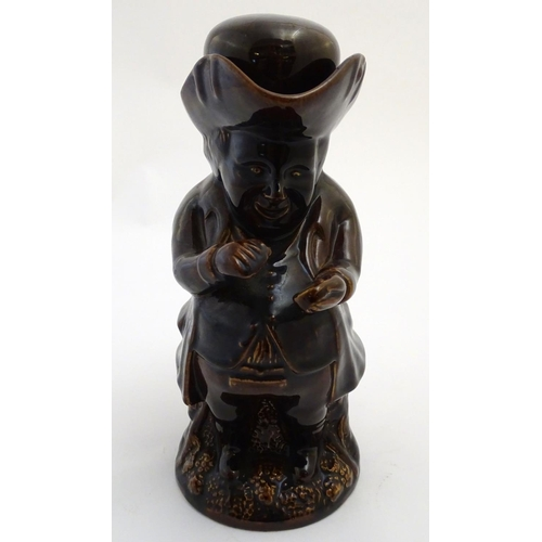33 - A Victorian Staffordshire treacle glaze Toby character jug, formed as the snuff taker. Approx. 10 1/...