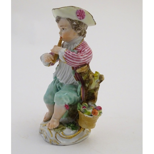 43 - A Continental porcelain figure of a boy playing a musical instrument, seated on a naturalistic base ...
