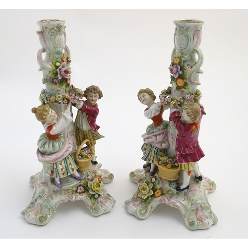 44 - A pair of 19thC German figural lamp bases with two figures arranging flowers, raised on a scrolling ...