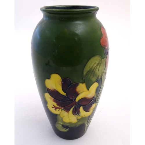 53 - A Moorcroft baluster vase in the hibiscus flower pattern. Impressed and painted marks under. Approx....