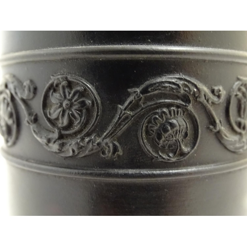 56 - A Wedgwood basalt ware cylindrical vase with classical decoration depicting Apollo in a landscape. I...