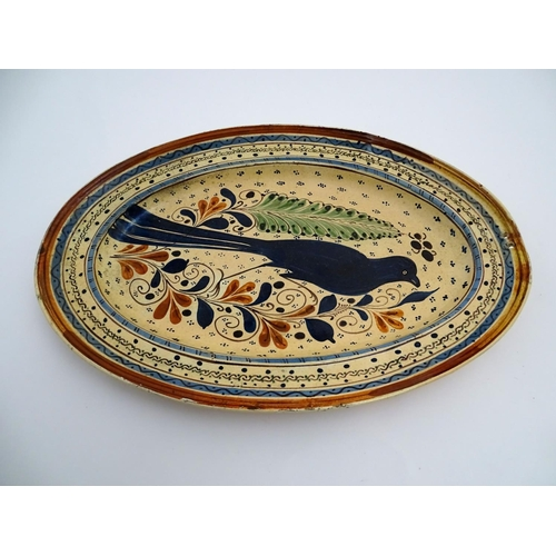 60 - A Swiss terracotta oval pottery dish with hand painted folk art decoration depicting a bird amongst ...