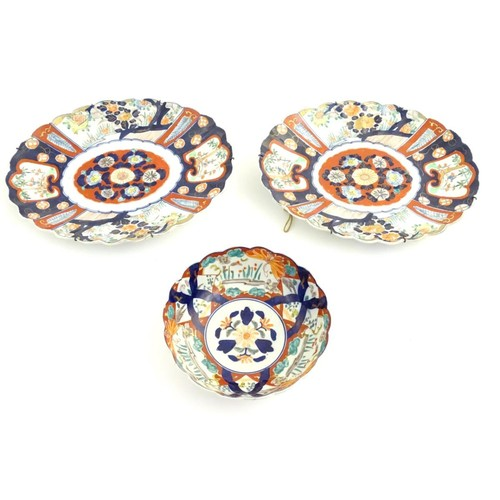 23 - Two Imari dishes of oval form with lobed rims, decorated with panelled flowers and landscapes with g...