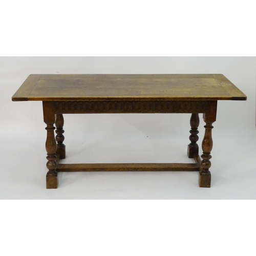 1193 - A c.1900 oak dining table with a planked top and turned supports with a box stretcher. Accompanied b...
