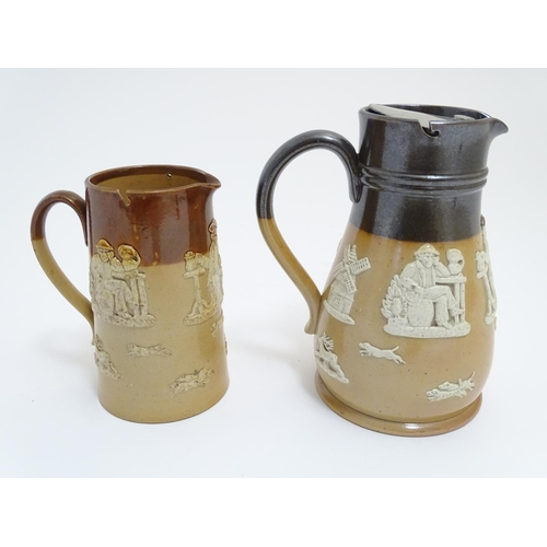 56 - A Royal Doulton and Doulton Lambeth two tone stoneware jugs decorated with hunting scenes in relief....