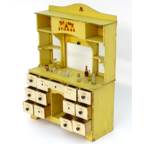 826 - Toy: A 20thC Tri-ang Stores dresser style child's wooden play shop the bottom section with 13 fitted...