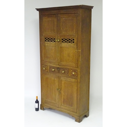 1195 - An early 19thC oak Welsh bread and cheese cupboard with a moulded cornice above quarter sawn oak doo...