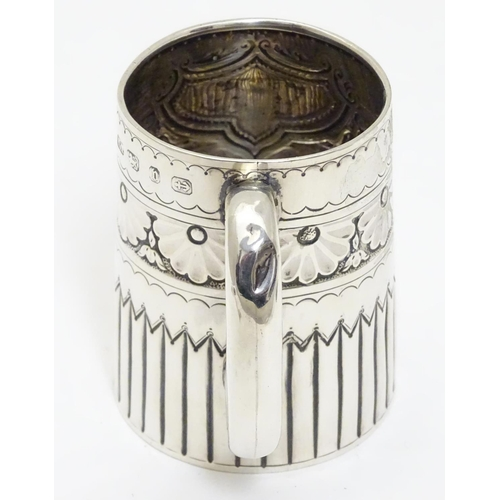 397 - A Victorian silver mug with embossed decoration and a loop handle. Hallmarked Birmingham 1895 maker ...