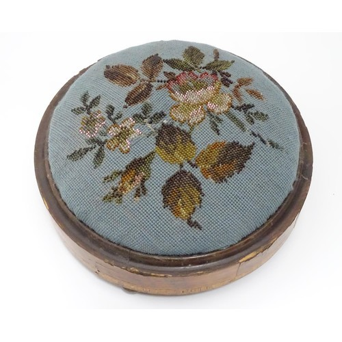 14 - A Victorian walnut footstool of circular form with bead decoration. Approx. 11