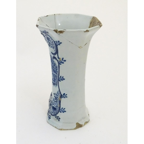 46 - An 18thC Delft blue and white octagonal vase with a flared rim, decorated with a vase of flowers and...