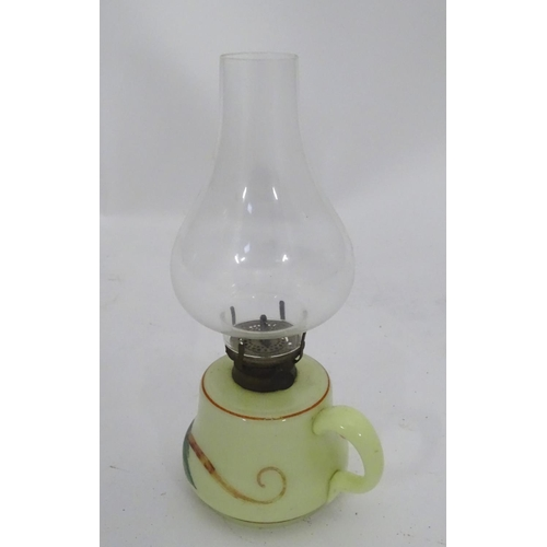 47 - A small glass oil lamp with floral decoration, loop handle and clear glass chimney. 10'' high overal...