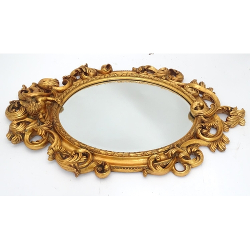 43 - A gilt mirror with cherub detail. Approx. 35 1/2