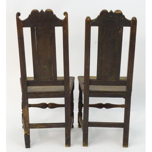 1295 - A pair of 17thC oak side chairs with shaped top rails, panelled backs and seats, standing on turned ...