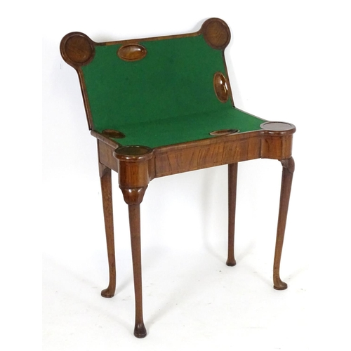 1255 - A George I walnut card table with castellated corners, opening to show a baize playing surface and c...