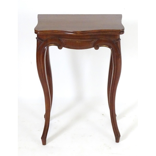 1256 - A small 19thC mahogany card table with a serpentine shaped rotating top opening to show baize playin...