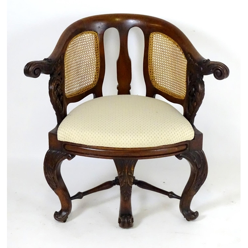 "A 19thC mahogany Bürgermeister chair with scrolled carved arms, double caned backrests and having three carved cabriole front legs terminating in scrolled feet. 35"" wide x 22"" deep x 32"" high."