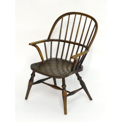 1293 - A mid 19thC childs Windsor chair with a double bow back above swept arms an elm seat and standing on...