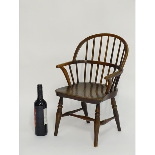 1294 - A mid 19thC childs Windsor chair with a double bow back above an elm seat and turned tapering legs u...