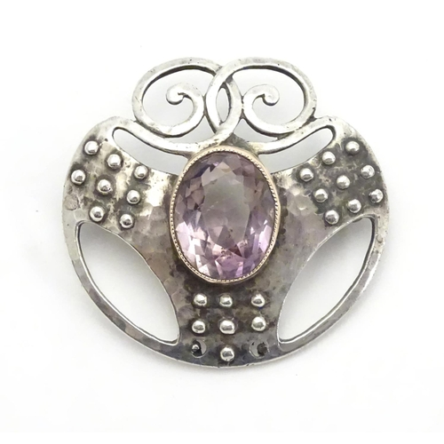 "Murrle Bennett & Co. : An Arts & Crafts .950 silver brooch with hammered decoration and set with central facet cut amethyst. Marked reverse 950 and MB Co. Approx. 1 1/4"" wide"