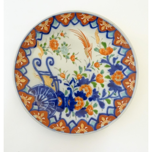 4 - An Oriental plate in the Imari palette decorated with flowers, foliage and an Asiatic pheasant. Impr...