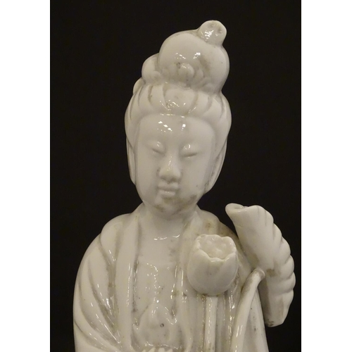 7 - A Chinese blanc de chine figure of Guanyin holding flowers, raised on a base of lotus flowers and li...