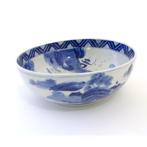 11 - A Chinese blue and white bowl with hand painted decoration depicting an Oriental landscape with pago...