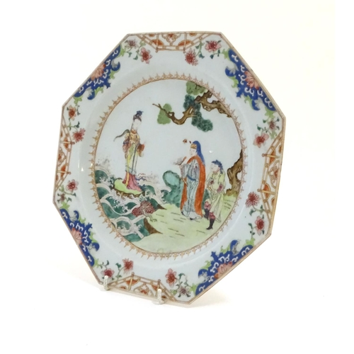 12 - A Chinese plate of octagonal form decorated in famille rose depicting figures in a coastal landscape...