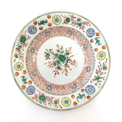 15 - A Chinese plate with central floral and foliate detail, with a patterned border with flowers and sty...