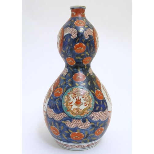 23 - An Oriental double gourd vase in the Imari palette with lobed panels depicting plants on a terrace, ...
