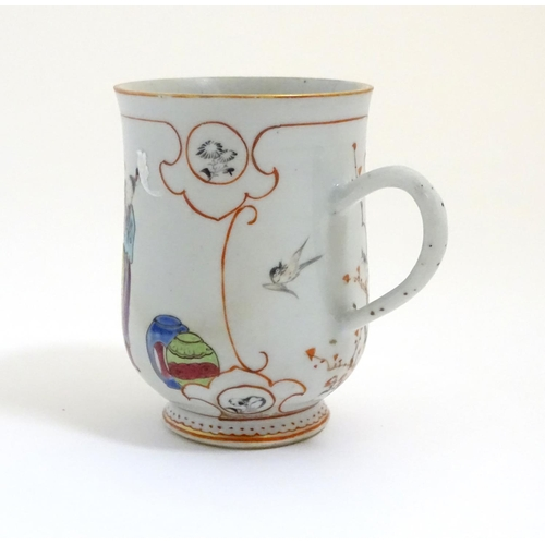 25 - A Chinese export famille rose mug / tankard decorated with figures in a domestic interior scene, and...