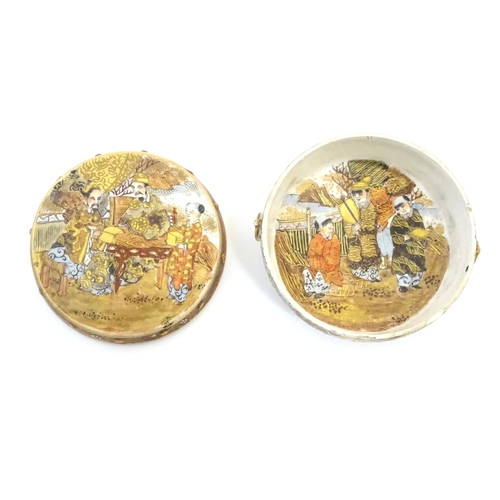 26 - A Japanese Satsuma pot and cover. The cover decorated with a landscape scene with two scholar figure...