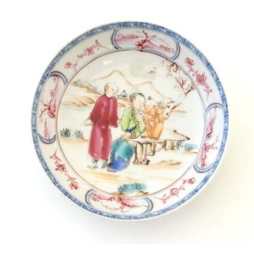 27 - An Oriental famille rose dish depicting a mountainous landscape scene with two figures and a child r...