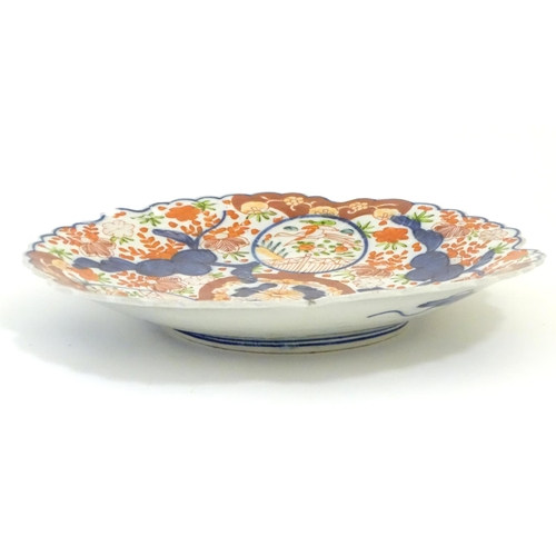 29 - A Japanese Imari plate with a scalloped rim with stylised leaf veins in relief to the centre, decora...