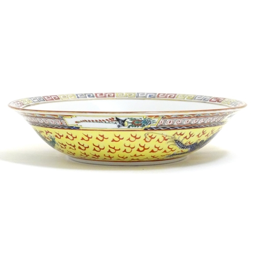 34 - A Chinese famille jeune bowl decorated with two dragons and patterned border. Character marks under....