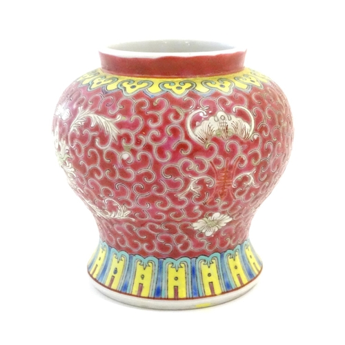39 - A Chinese famille rose squat vase with a flared base, the body with floral motifs and stylised bat d...