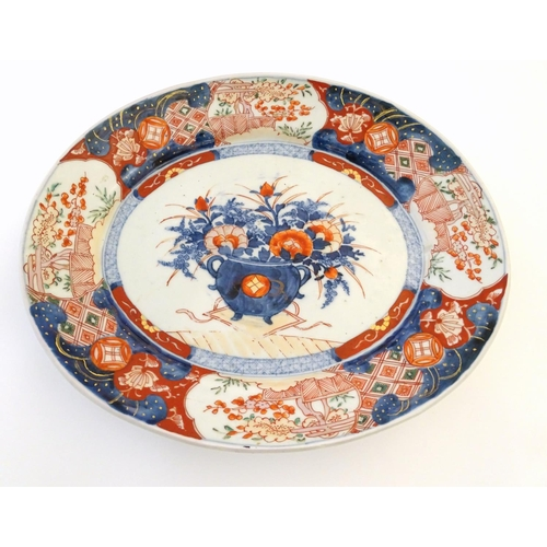 42 - A Japanese Imari style plate, the centre decorated with a vase of flowers with a floral border. Appr...