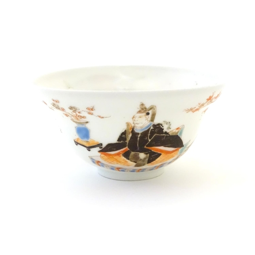 44 - A Japanese small bowl depicting seated figures, a male figure in robes to one side, and a female fig...
