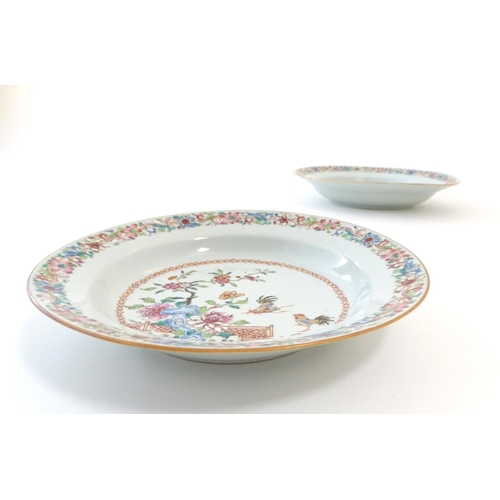 48 - A pair of Chinese dishes decorated with a garden / terrace scene with flowers and foliate with two c...