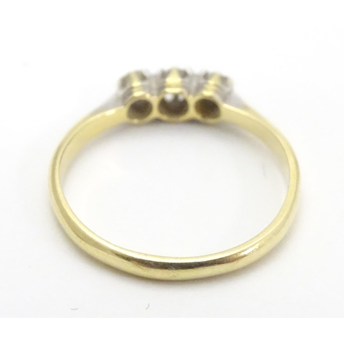 552 - An 18ct gold ring set with trio of diamonds. Ring size approx M...