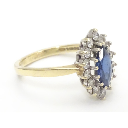 553 - A 14k gold ring set with central sapphire bordered by white stones. Ring size approx N 1/2...