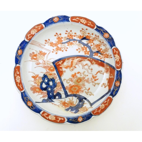 10 - A pair of Japanese plates / dishes with lobed rims in the Imari palette with hand painted decoration...
