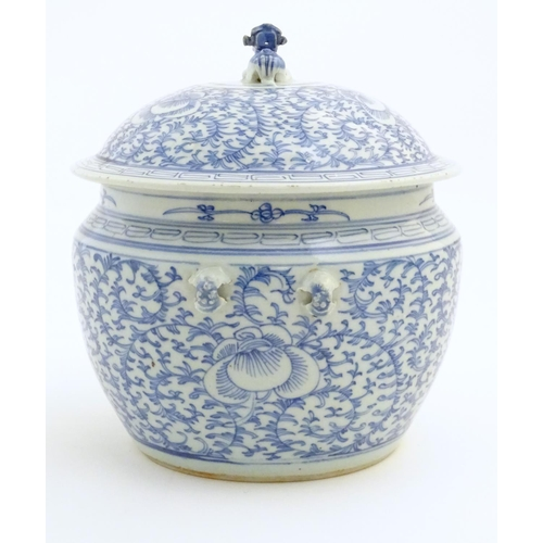 28 - A Chinese blue and white pot and cover with scrolling floral and foliate detail. The lid surmounted ...