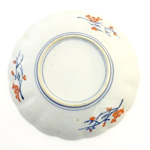 3 - A Japanese plate with a lobed rim, hand painted in the Imari palette with stylised flowers and birds...