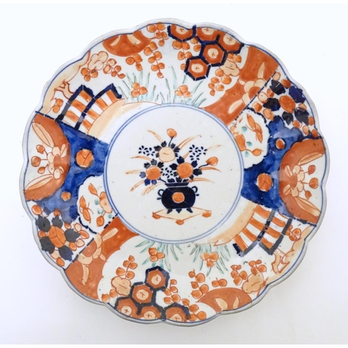 32 - Two Japanese plates decorated in the Imari pattern with central floral design. The outer with floral...